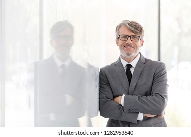 Portrait of smiling mature businessman with arms crossed leaning on wall at office