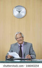 Portrait of a smiling mature businessman with documents at desk in office