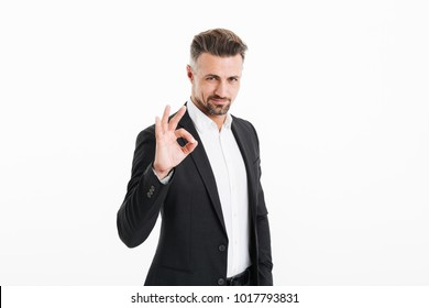 Portrait of a smiling mature businessman dressed in suit showing ok gesture isolated over white background