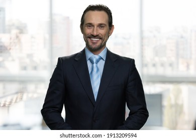 Portrait of smiling mature businessman in office. Huge blurred office windows on the background.
