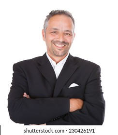 Portrait of smiling mature businessman standing arms crossed over white background