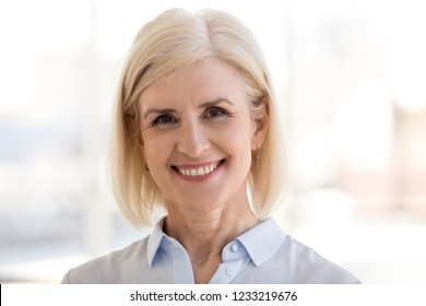 Portrait of smiling mature businesswoman with beautiful face, happy middle aged attractive woman looking at camera, senior confident trusted female professional, friendly older lady headshot
