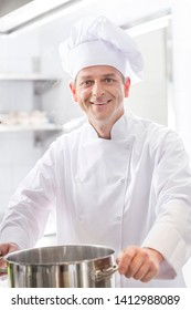 Portrait of smiling mature chef with steel cooking pot in kitchen at restaurant