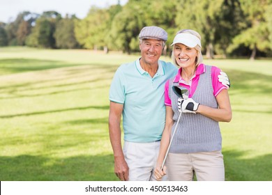 Portrait of smiling mature couple standing at golf course