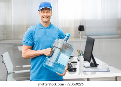 Portrait Of A Smiling Mature Delivery Man Holding Large Water Bottle In Office