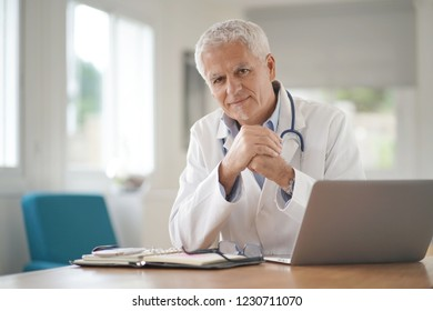 Portrait of smiling mature doctor at work