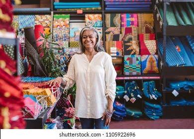 Portrait of a smiling mature fabric shop owner standing by racks and shelves full of colorful cloths and textiles