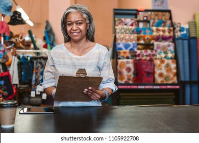Portrait of a smiling mature fabric shop owner standing behind a counter surrounded by colorful cloths and textiles and holding a clipboard