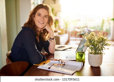Portrait of a smiling mature female entrepreneur sitting at a table in her home office working on a laptop