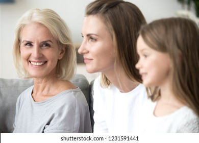 Portrait of smiling mature grandmother looking at camera near young daughter and kid granddaughter looking forward to good future, three 3 women family, older elderly generation getting old concept