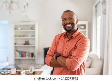 Portrait of smiling mature man with beard standing with crossed arms. Confident african man with folded arms at home looking at camera. Happy senior in casual feeling good.