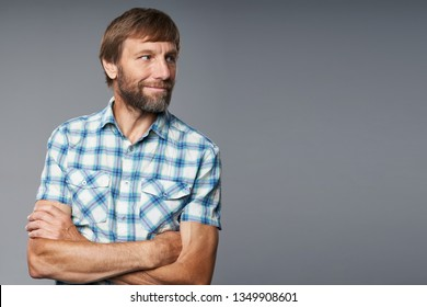 Portrait of smiling mature man in checkered shirt, looking to side, over grey studio background
