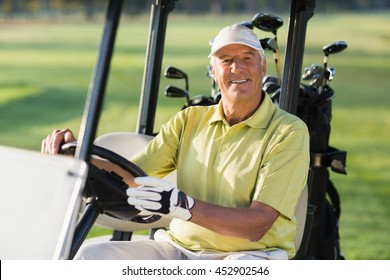 Portrait of smiling mature man driving golf buggy on field