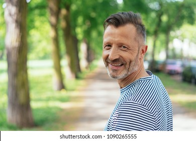 Portrait of smiling mature man standing in park on sunny day