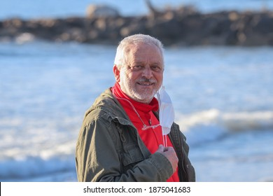 Portrait of smiling mature man taking off his surgical mask, on marine background.