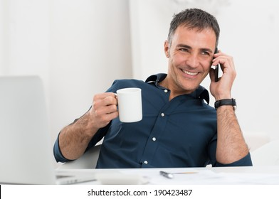 Portrait Of Smiling Mature Man Talking On Cellphone Holding Coffee Cup