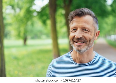 Portrait of smiling mature man wearing striped t-shirt standing in park