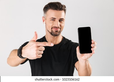Portrait of a smiling mature sportsman showing blank screen mobile phone and pointing finger isolated over gray background