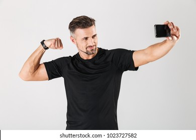 Portrait of a smiling mature sportsman taking a selfie and showing muscles isolated over gray background