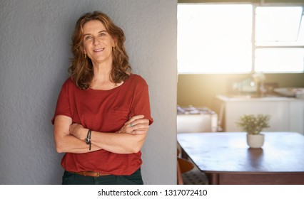 Portrait of a smiling mature woman leaning with her arms crossed against a wall in her sunny home