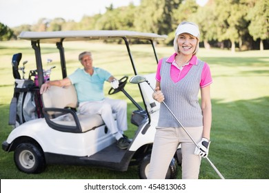 Portrait of smiling mature woman standing by man in golf buggy