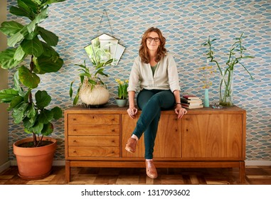 Portrait of a smiling mature woman wearing glasses sitting on a cabinet in her stylish apartment