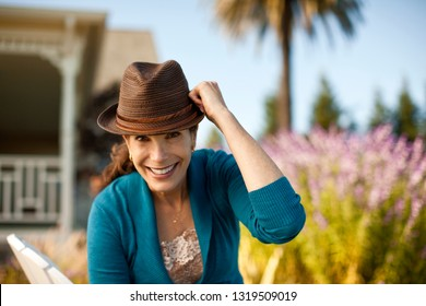c5ba7c59 Portrait of smiling mature woman wearing fedora hat in her backyard.