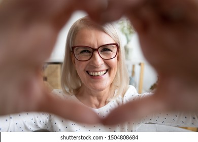 Portrait smiling mature woman wearing glasses looking through heart shaped hands close up, expressing love, making video call, older female having fun, posing for photo, vlogger recording vlog