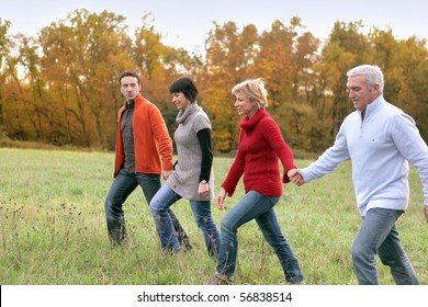Portrait of smiling men and women having a walk in the countryside
