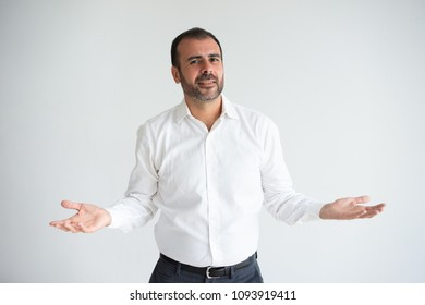 Portrait of smiling mid adult businessman shrugging shoulders. Puzzled Caucasian bearded man wearing white shirt. Ignorance and advertising concept