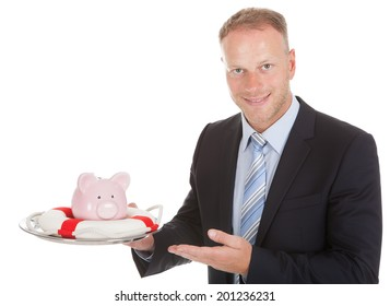 Portrait of smiling mid adult businessman protecting piggybank with lifebuoy over white background