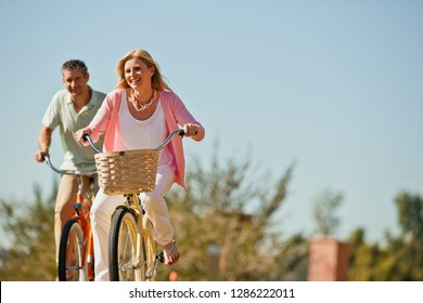 Portrait of a smiling mid adult woman riding a bicycle with her husband.