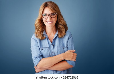 Portrait of smiling middle age woman wearing casual clothing while standing against isolated background and looking at camera.
