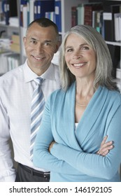Portrait of a smiling middle aged business couple in office