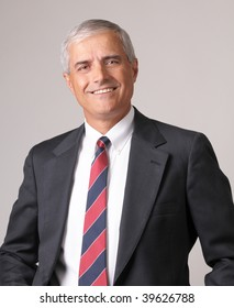 Portrait of a Smiling Middle Aged  Businessman against a gray background