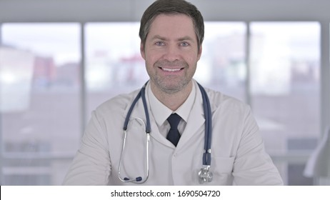 Portrait of Smiling Middle Aged Doctor Looking at the Camera