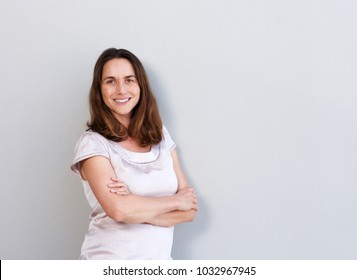 Portrait of smiling middle aged woman against white wall