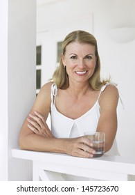 Portrait of a smiling middle aged woman with water glass leaning on verandah balustrade