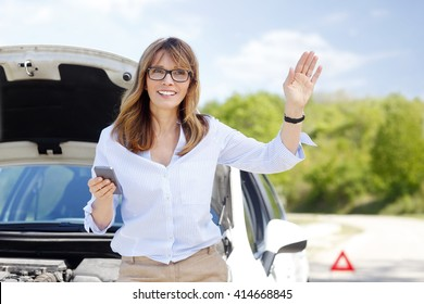 Portrait of smiling middle aged woman waiting for roadside assistance service while standing at her broken down car.