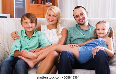 Portrait of smiling middle class family with two children at home interior. Focus on woman