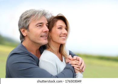 Portrait of smiling middle-aged couple in countryside