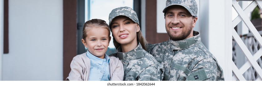 Portrait of smiling military mother and father with daughter looking at camera with house on background, banner