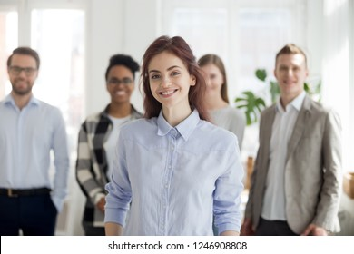 Portrait of smiling millennial female employee or worker looking at camera, happy successful woman standing foreground posing with colleagues at background, student or intern make picture in office