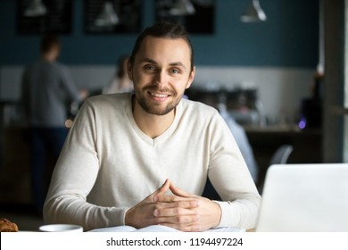 Portrait of smiling millennial man sitting in café with laptop and books on table, happy young guy work in coffeeshop using computer, male student look at camera busy preparing report in coffeehouse