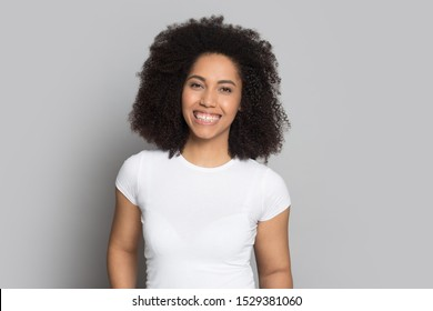 Portrait of smiling mixed race ethnicity young woman in white t-shirt isolated on grey studio background, happy african American millennial girl with curly hair and white teeth look at camera