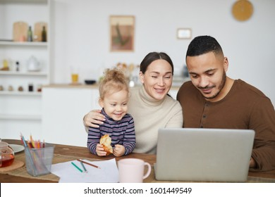 Portrait of smiling mixed race family using laptop together while shopping online, copy space