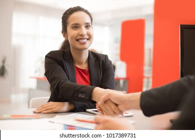 Portrait of smiling mixed-race businesswoman shaking hands with partner after closing successful deal during meeting in modern office