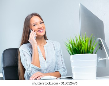 Portrait of smiling modern business woman in office using her mobile phone.