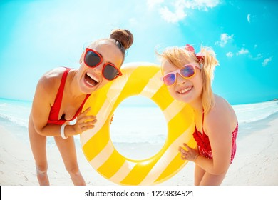 Portrait of smiling modern mother and child in red swimwear on the beach holding yellow inflatable lifebuoy