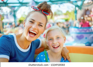 Portrait of smiling modern mother and child tourists in theme park enjoying attraction.
